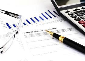concetto di affari con penna stilografica e occhiali da vista e calcolatrice foto
