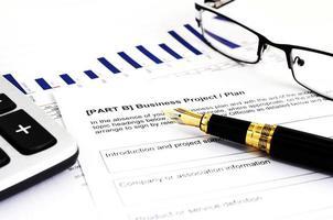 piano di progetto aziendale con penna stilografica, calcolatrice e occhiali da vista foto