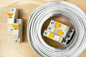 la bobina di fili e gli interruttori automatici giacciono su un compensato foto