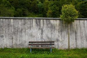 panchina vuota con un vecchio muro foto