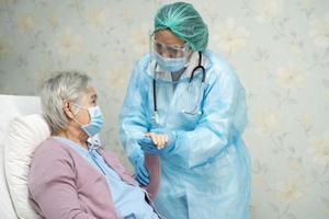 medico asiatico che indossa una protezione per il viso e una tuta protettiva nuova normale per controllare il paziente protegge la sicurezza infezione covid 19 focolaio di coronavirus nel reparto infermieristico di quarantena foto
