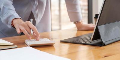 Close up di imprenditrice ragioniere o banchiere fare calcoli finanziamento aziendale contabilità concetto bancario foto