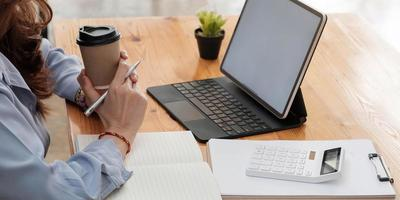 ritratto di donna d'affari sul posto di lavoro con computer portatile e blocco note foto