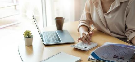 donna d'affari che lavora in finanza e contabilità analizzare il bilancio finanziario con calcolatrice e computer portatile in ufficio foto