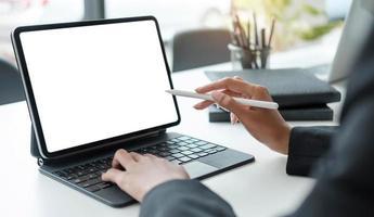 chiudere le mani della donna designer utilizzando la tavoletta digitale per lavorare a casa o in ufficio foto