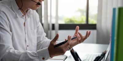 giovane insegnante allenatore indossando le cuffie parlando tenendo lezione online studente concentrato guardando lo schermo del monitor del computer foto