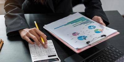 donna con la relazione finanziaria e la calcolatrice donna che utilizza la calcolatrice per calcolare la relazione al tavolo in ufficio foto