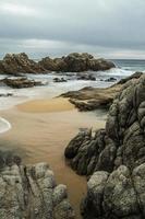 paesaggio marino nuvoloso su una spiaggia rocciosa foto