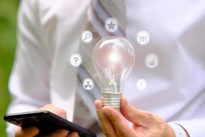 uomo d & # 39; affari che tiene la lampadina e il concetto di innovazione tecnologica foto