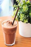 frullato di cacao sulla tavola di legno con pianta artificiale foto