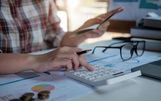 dati finanziari analizzando la scrittura a mano e il conteggio sulla calcolatrice in ufficio sulla scrivania in legno foto