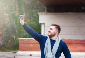 giovane che scatta una foto con il suo telefono cellulare nel parco