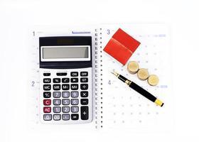 calcolatrice e penna stilografica e monete pila e casa di carta sulle pagine del libro del calendario per il concetto di mutui per la casa foto