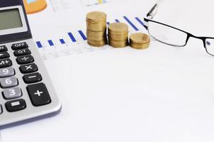 salvadanaio blu e pila di monete e casa di carta gialla per il concetto di risparmio di denaro foto