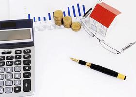 concetto di casa laons con penna stilografica e carta casa e monete pila e occhiali da vista e calcolatrice sul documento di report foto