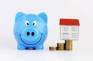 concetto di piano di risparmio di denaro con salvadanaio blu e casa di carta sulla pila di monete su sfondo bianco foto