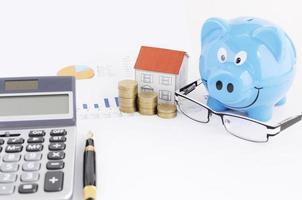 piano di risparmio di denaro con salvadanaio e casa di carta e occhiali da vista e calcolatrice e penna stilografica foto