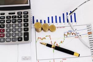 pila di monete e penna stilografica affari e occhiali da vista e calcolatrice per il concetto di investitore azionario foto