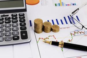 concetto di investitore azionario con penna stilografica affari e pila di monete e occhiali da vista e calcolatrice foto