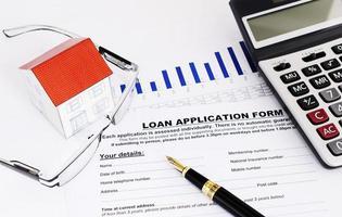 concetto di mutui ipotecari con penna stilografica e occhiali da vista e casa di carta e calcolatrice e documento di modulo di domanda di prestito foto