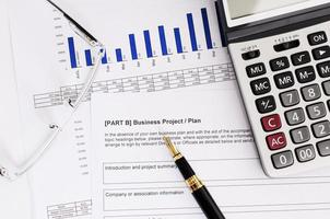 concetto di affari con penna stilografica e occhiali da vista e calcolatrice sul piano aziendale foto