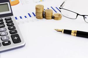 concetto di affari e finanza con stretta di penna stilografica e pila di monete e occhiali da vista e calcolatrice foto