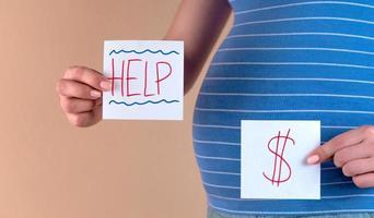 una vista ravvicinata della pancia di una donna incinta con le parole aiutare e un segno di dollaro foto