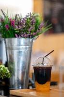 un bicchiere di caffè arancione sul tavolo nella caffetteria foto