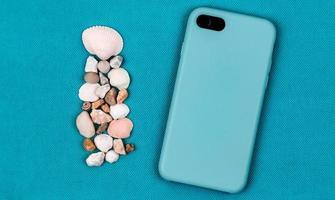 lato posteriore dello smartphone in custodia blu acqua su uno sfondo acqua alla moda con conchiglie di mare foto