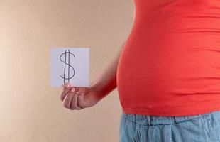 una vista ravvicinata della pancia di una donna incinta in rosso che tiene in mano un foglio di carta bianco con il simbolo del dollaro foto