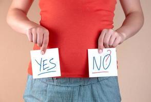 una vista ravvicinata della pancia di una donna incinta con due fogli con le iscrizioni sì e no foto