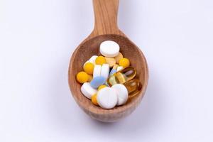 pillole medicinali e droga in un cucchiaio di legno su sfondo bianco con spazio di copia foto