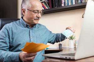 uomo anziano che lavora con il portatile a casa sfogliando fatture e documenti foto