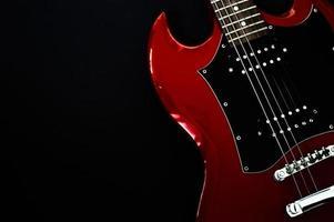 closeup chitarra elettrica rossa su sfondo nero foto