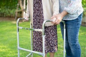 aiutare e prendersi cura della donna anziana asiatica o anziana anziana usa il deambulatore con forte salute mentre si cammina al parco in felice vacanza fresca foto