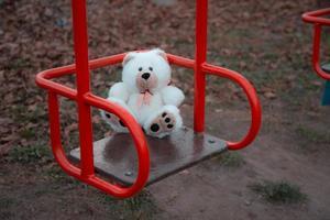 primo piano di un orsacchiotto seduto su un'altalena per bambini foto