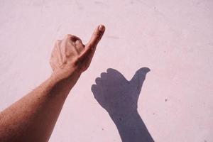 gesticolando con la mano sul muro rosa foto