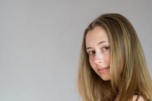 Close up ritratto in studio di una giovane donna tornata indietro girando la testa guardando la telecamera su sfondo grigio foto