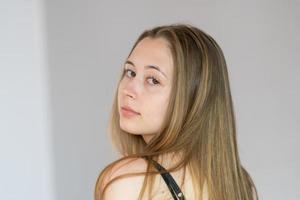 Close up ritratto in studio di una giovane donna tornata indietro girando la testa guardando la telecamera foto