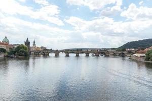 Vista panoramica del ponte Carlo medievale ad arco in pietra ponte che attraversa il fiume Moldava Moldava a Praga Repubblica Ceca foto