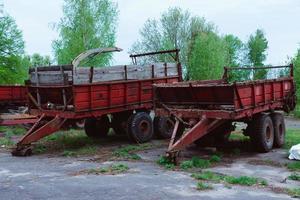 vecchi trattori e altro materiale agricolo su un deposito di rottami foto