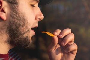 uomo barbuto nella foresta che mangia patatine foto