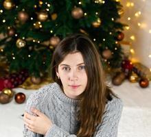 giovane bella donna alla moda in vestito lavorato a maglia grigio vicino all'albero di Natale foto