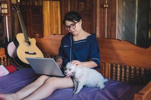 giovane donna che lavora al computer portatile a casa carino piccolo cane oltre a lavorare da casa foto