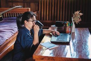 donna che mangia un caffè seduto su un pavimento in casa annotare appunti aperto laptop davanti al suo concetto di home office foto