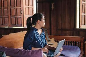 giovane donna che lavora seduto sul divano con il portatile a casa foto