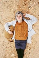 Un avventuriero giovane donna caucasica sdraiato su un terreno di sabbia accanto a uno zaino che indossa un maglione di lana e berretto con gli occhi chiusi e l'arancione come colore principale foto