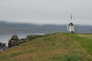 mulino a vento e bandiera islandese nell'isola di vigur in una giornata nuvolosa e ventosa Islanda foto