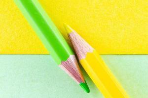 matite colorate su fogli di colore giallo e verde disposti in diagonale foto