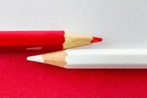 matite colorate su carte a colori rosse e bianche disposte orizzontalmente foto